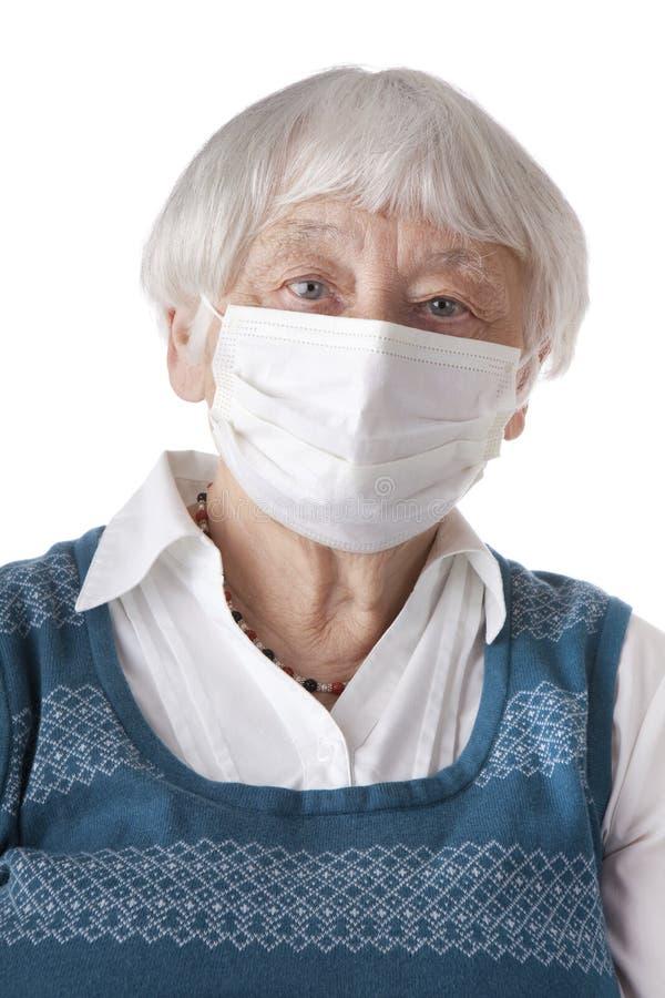 Mujer mayor con la máscara de la gripe foto de archivo libre de regalías