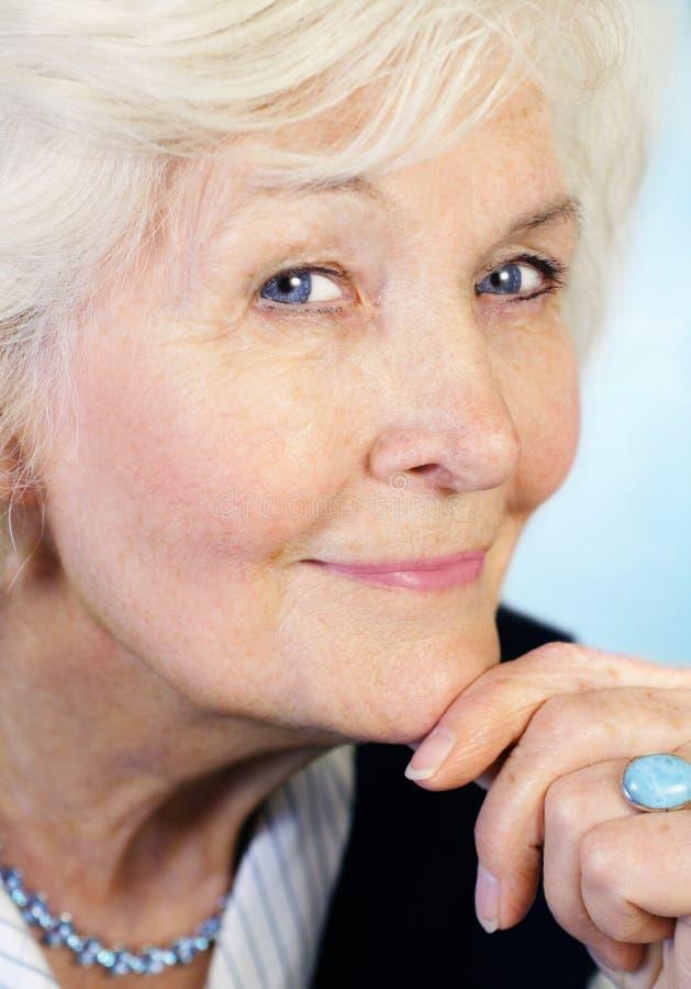 Mujer mayor con la mano en la barbilla imagen de archivo libre de regalías
