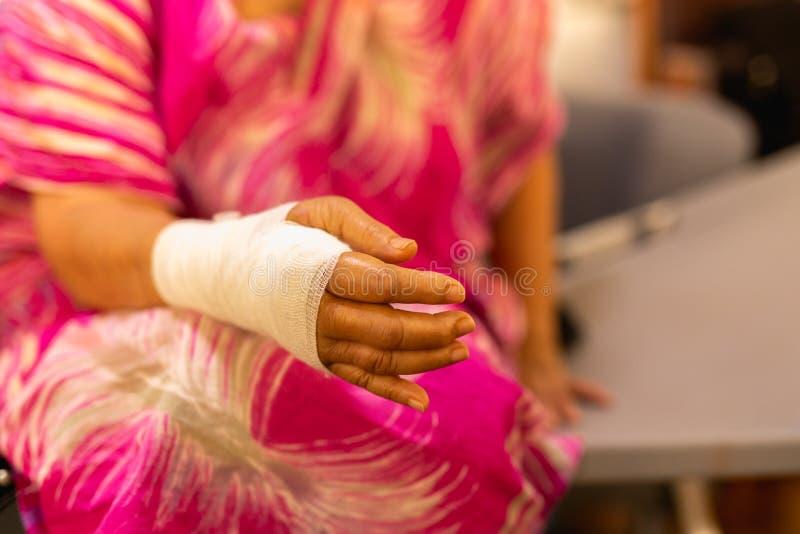 Mujer mayor con la mano herida en el vendaje que descansa en casa fotos de archivo