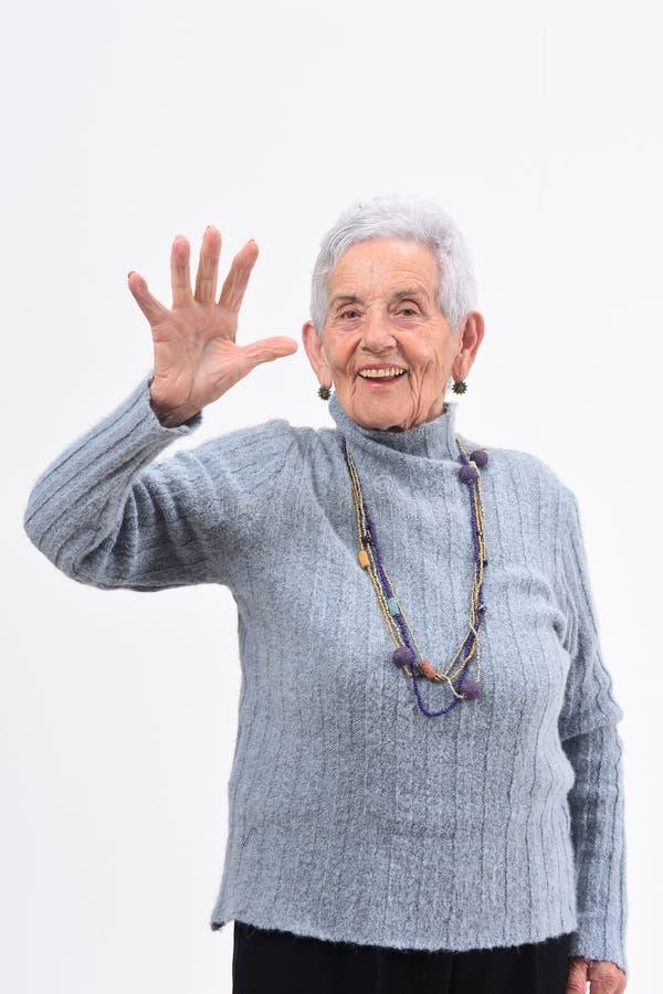 Mujer mayor con la mano y el número abiertos cinco en el fondo blanco imagen de archivo