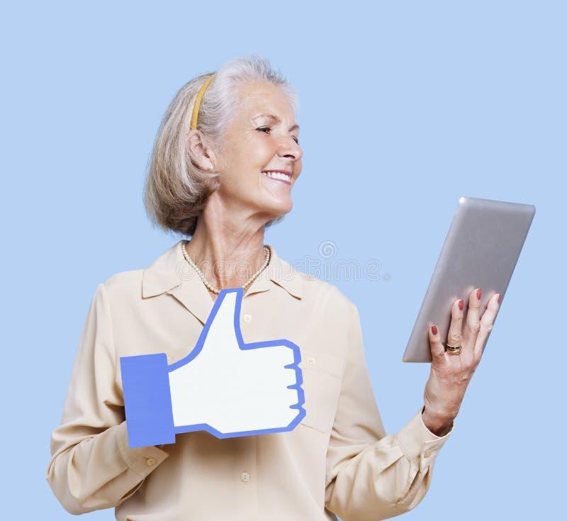 Mujer mayor con la PC de la tableta que se considera falsa como el botón contra fondo azul imagen de archivo libre de regalías