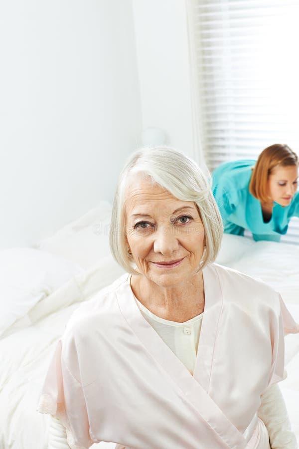 Mujer mayor con la señora de la limpieza en casa foto de archivo