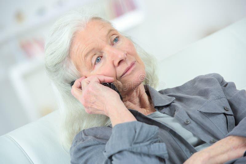 Mujer mayor con la sensación del teléfono mal fotos de archivo