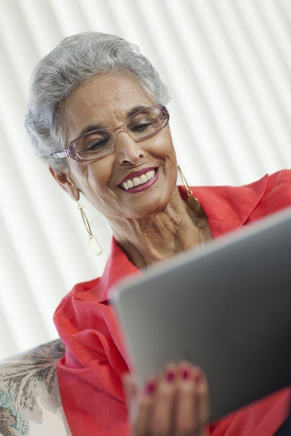 Mujer mayor con la tablilla de Digitaces fotos de archivo libres de regalías