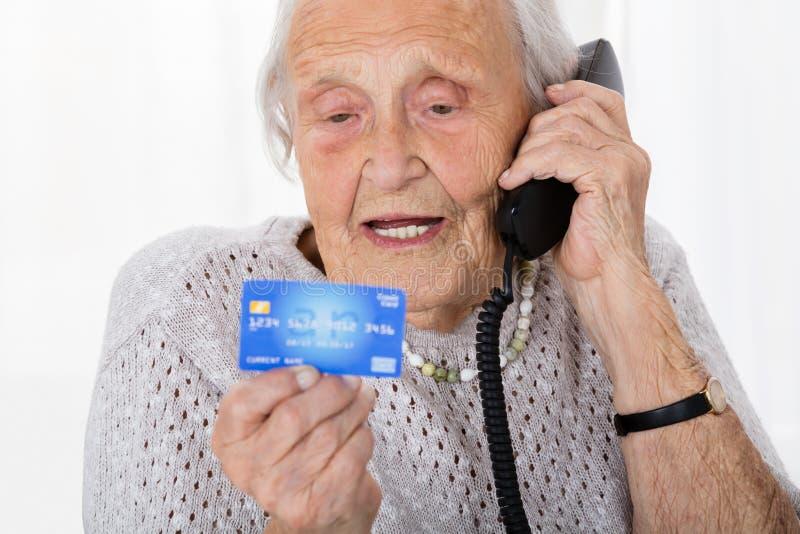 Mujer mayor con la tarjeta de crédito en el teléfono imagenes de archivo