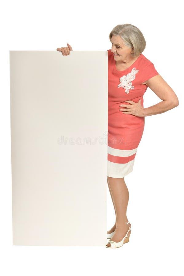 mujer mayor con la tarjeta en blanco imagenes de archivo