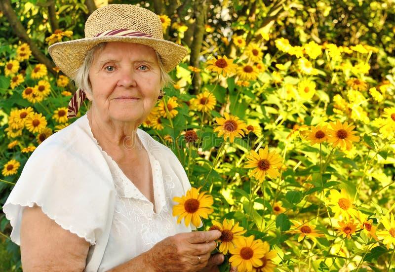 Mujer mayor con las flores. fotos de archivo
