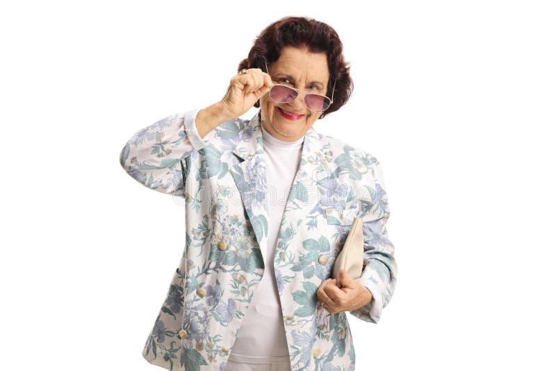 Mujer mayor con las gafas de sol que sonríe en la cámara foto de archivo