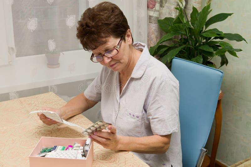 Mujer mayor con las píldoras y las instrucciones fotografía de archivo