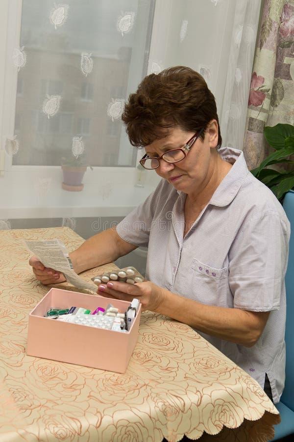 Mujer mayor con las píldoras y receta imagen de archivo