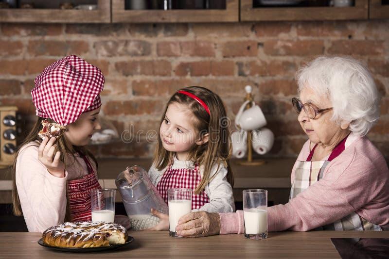 Mujer mayor con los nietos que sonríen y que prueban la empanada imágenes de archivo libres de regalías