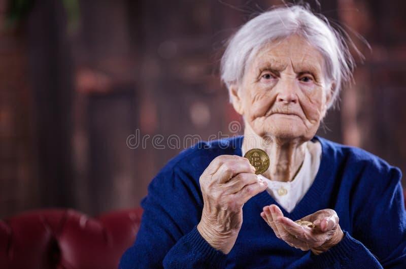 Mujer mayor con los pares de bitcoins, demostrando uno de ellos imagenes de archivo