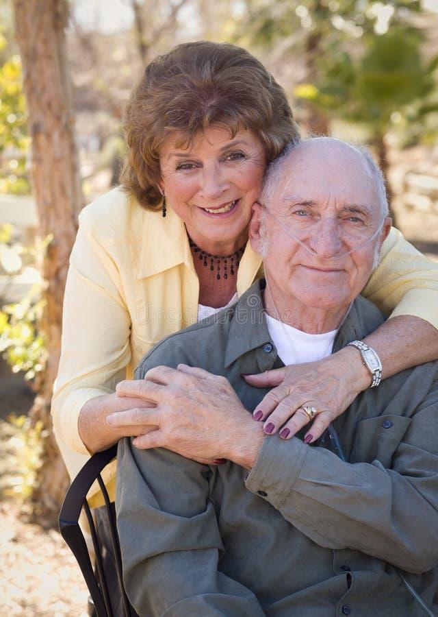 Mujer mayor con los tubos del oxígeno del hombre que desgastan imagen de archivo