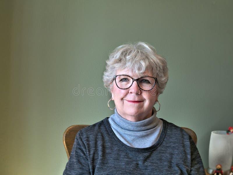 Mujer mayor con los vidrios que miran la cámara y la sonrisa imagen de archivo libre de regalías