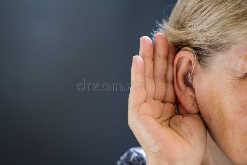 Mujer mayor con pérdida de oído en fondo gris Relativo a la edad imagen de archivo