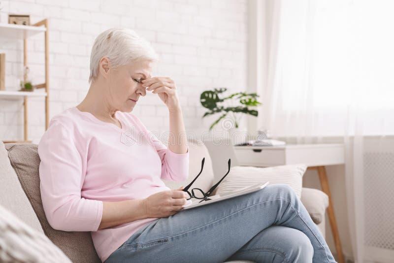 Mujer mayor con problemas de la visi?n usando la tableta imágenes de archivo libres de regalías