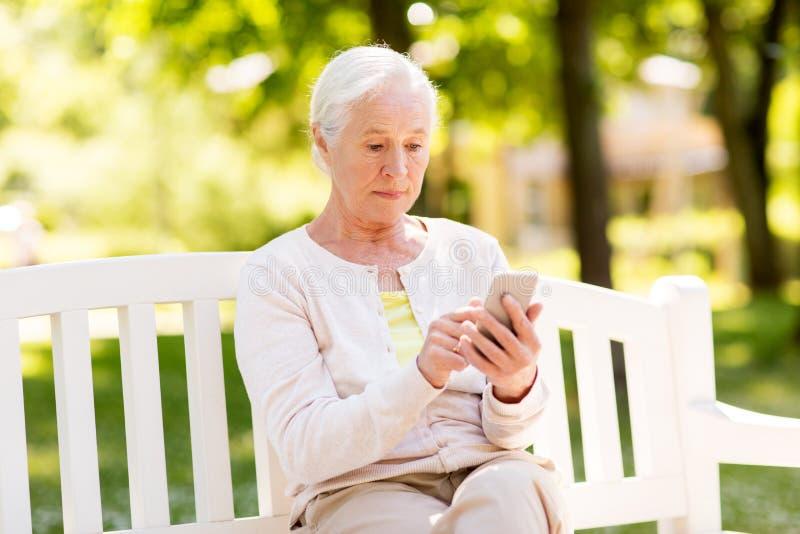 Mujer mayor con smartphone en el parque del verano imagen de archivo