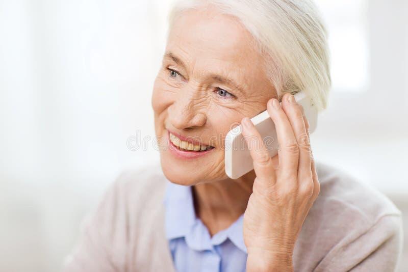 Mujer mayor con smartphone que llama en casa foto de archivo libre de regalías