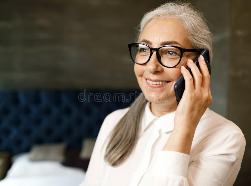 Mujer mayor con smartphone imagen de archivo