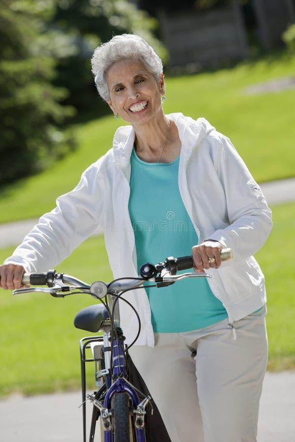 Mujer mayor con su bicicleta imagen de archivo libre de regalías
