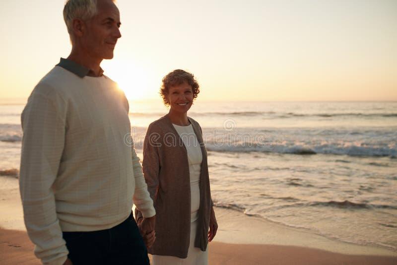 Mujer mayor con su marido que da un paseo en la playa fotos de archivo libres de regalías