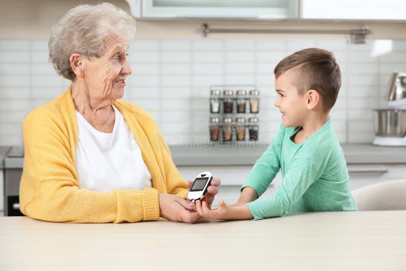 Mujer mayor con su nieto que usa glucometer digital en casa fotos de archivo libres de regalías