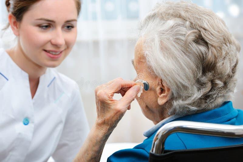 Mujer mayor con un audífono imagen de archivo