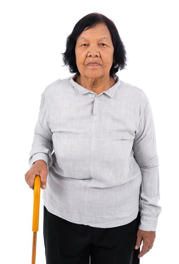 Mujer mayor con un bastón que camina aislado en el fondo blanco foto de archivo libre de regalías