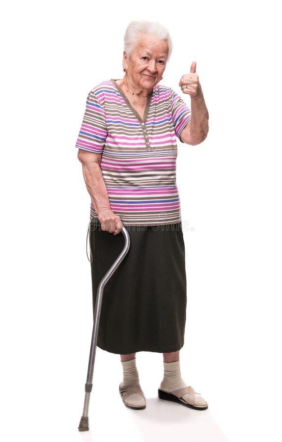 Mujer mayor con un bastón que muestra la muestra aceptable imágenes de archivo libres de regalías