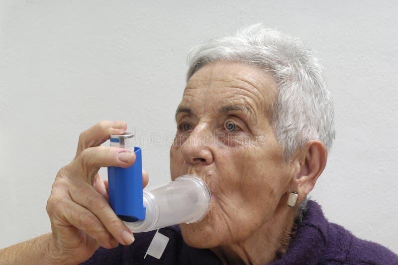 Mujer mayor con un inhalador imagen de archivo