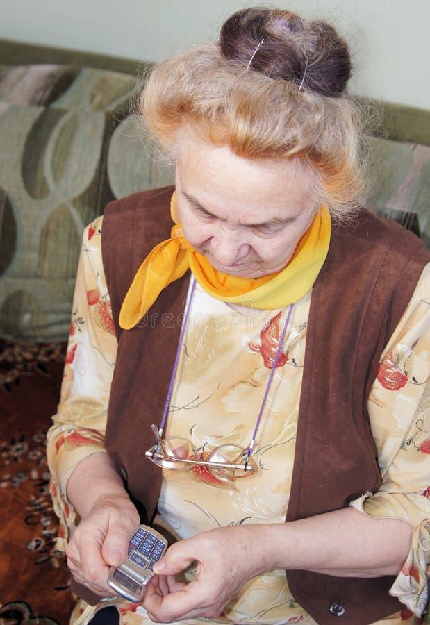 Mujer mayor con un móvil fotos de archivo