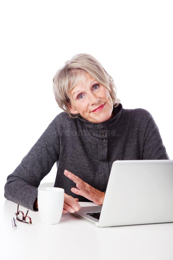 Mujer mayor con un ordenador portátil que encoge hombros imagenes de archivo