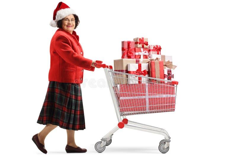 Mujer mayor con un sombrero de la Navidad que empuja un carro de la compra con los presentes y que mira la cámara fotografía de archivo libre de regalías