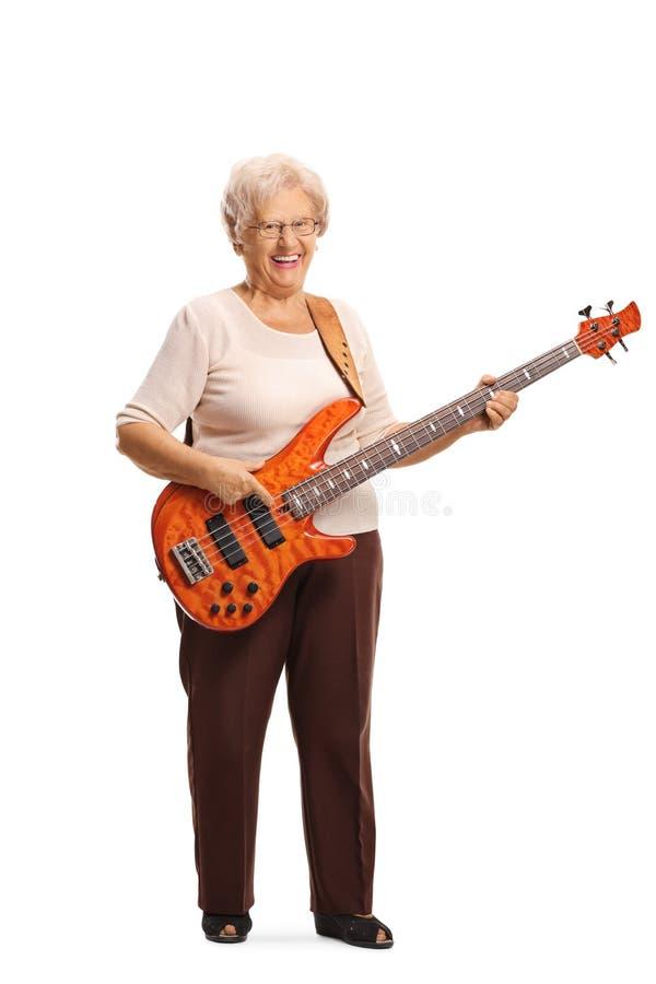 Mujer mayor con una guitarra baja eléctrica que sonríe en la cámara fotos de archivo