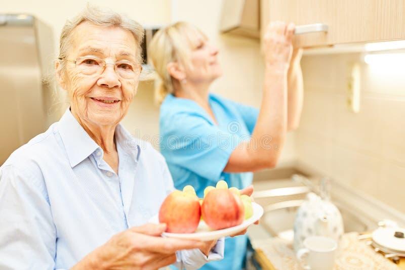 Mujer mayor con una placa de la fruta en la cocina fotos de archivo