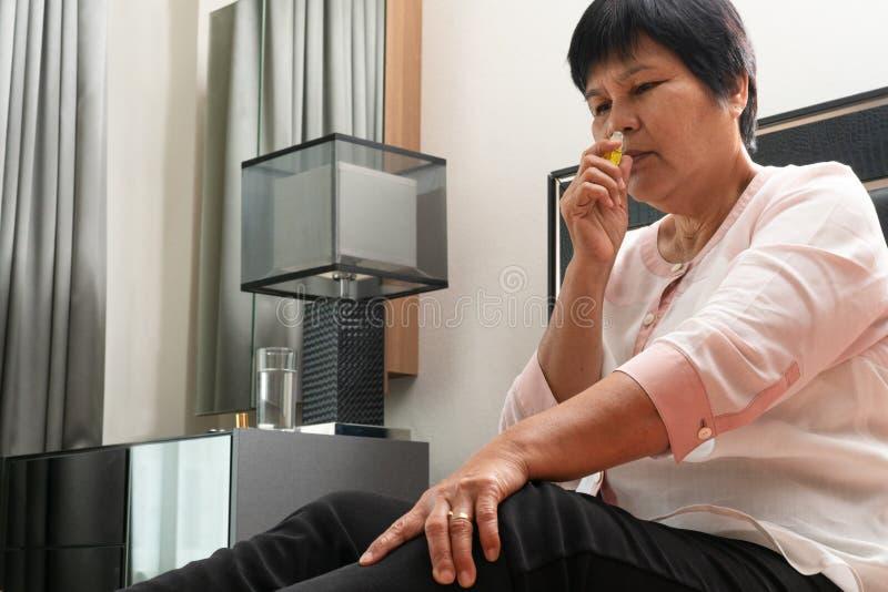 Mujer mayor con vértigos del headhache y sales que huelen fotos de archivo