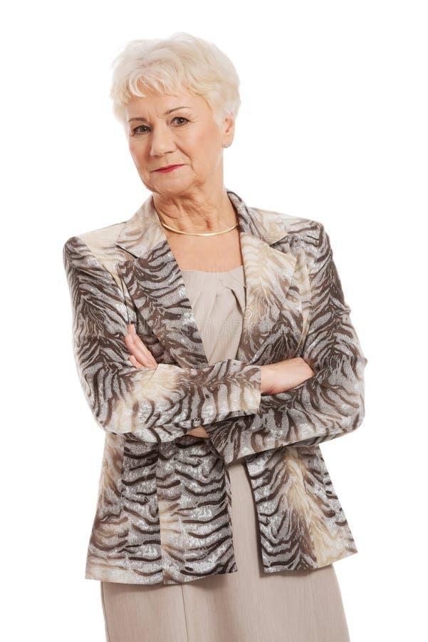 Mujer mayor confiada con los brazos doblados fotografía de archivo