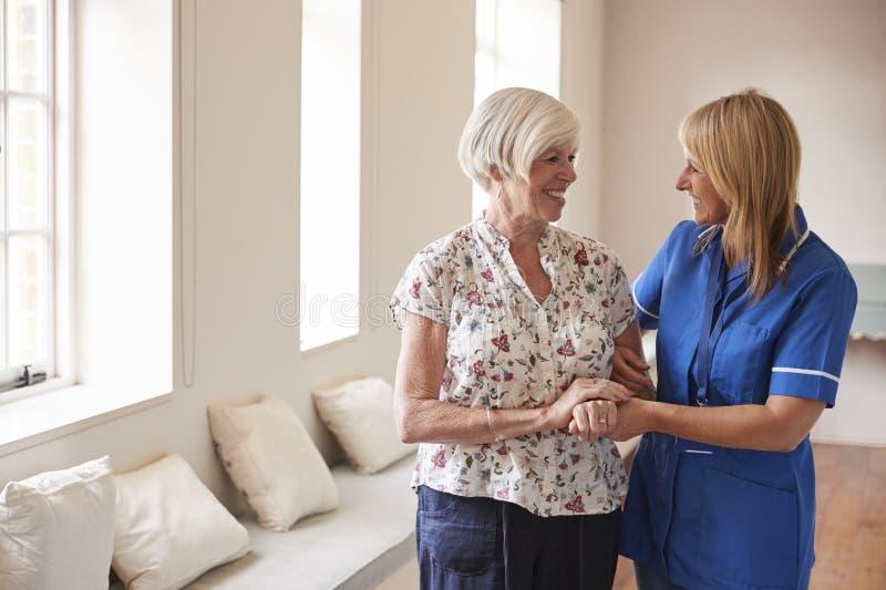 Mujer mayor confortada por la enfermera en la casa de retiro imagen de archivo libre de regalías