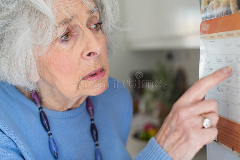 Mujer mayor confusa con la demencia que mira el calendario de pared imagen de archivo libre de regalías