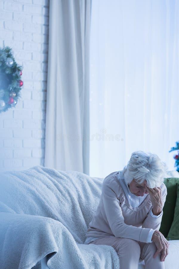 Mujer mayor de la desesperación en el sofá foto de archivo libre de regalías