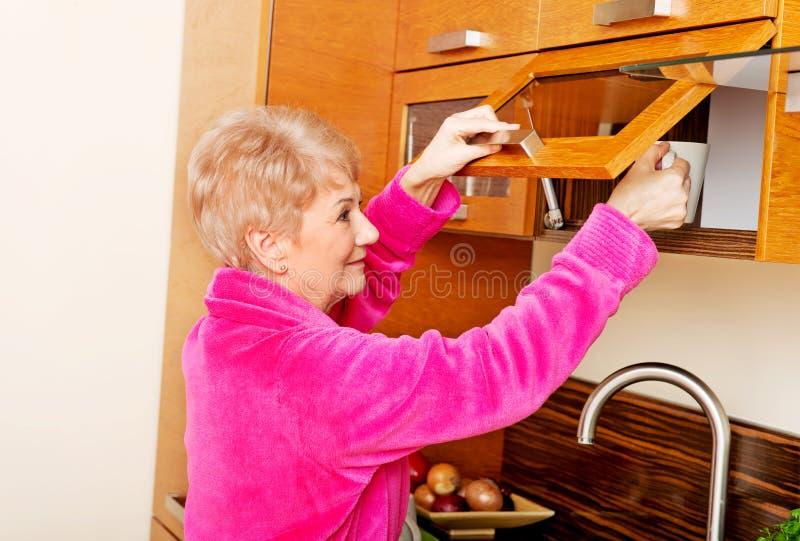 Mujer mayor de la sonrisa que toma la taza de un armario de cocina fotografía de archivo libre de regalías