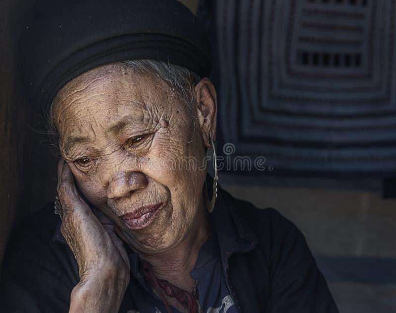 Mujer mayor de la tribu de Hmong que se relaja dentro de su casa en su pueblo en Sapa, Vietnam imágenes de archivo libres de regalías