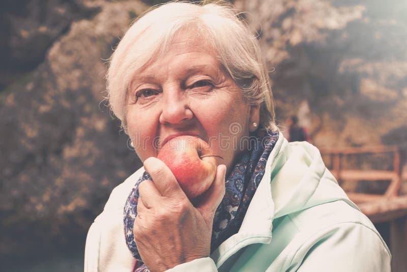 Mujer mayor de mirada sana con el pelo gris que come la manzana afuera imagen de archivo