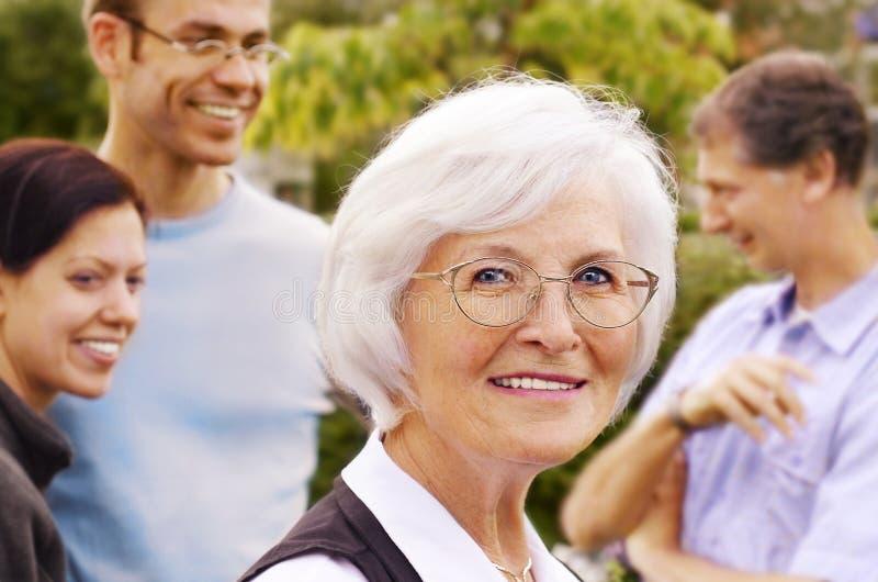 Mujer mayor delante del grupo de la gente joven fotografía de archivo