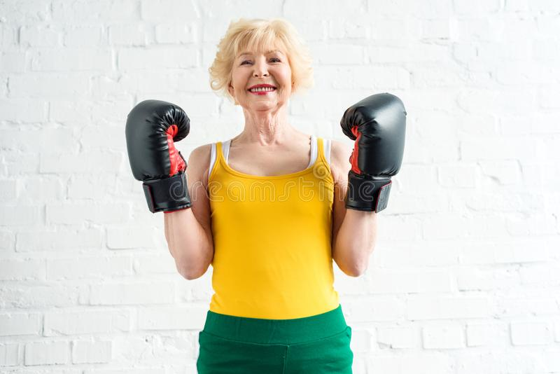 mujer mayor deportiva feliz en la sonrisa de los guantes de boxeo fotos de archivo