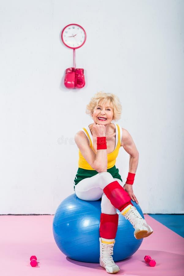 mujer mayor deportiva feliz que se sienta en bola y la sonrisa de la aptitud fotos de archivo