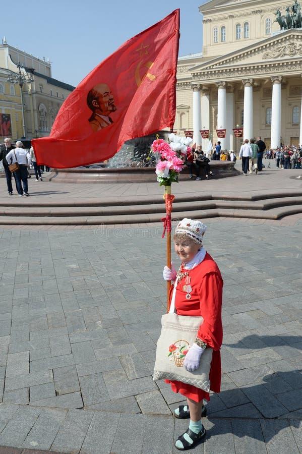 Mujer mayor desconocida con una bandera roja en el teatro de Moscú Bolshoi el día de la victoria imagen de archivo libre de regalías