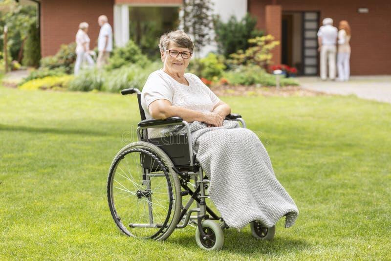 Mujer mayor discapacitada feliz en una silla de ruedas en duri de la hierba verde fotografía de archivo libre de regalías