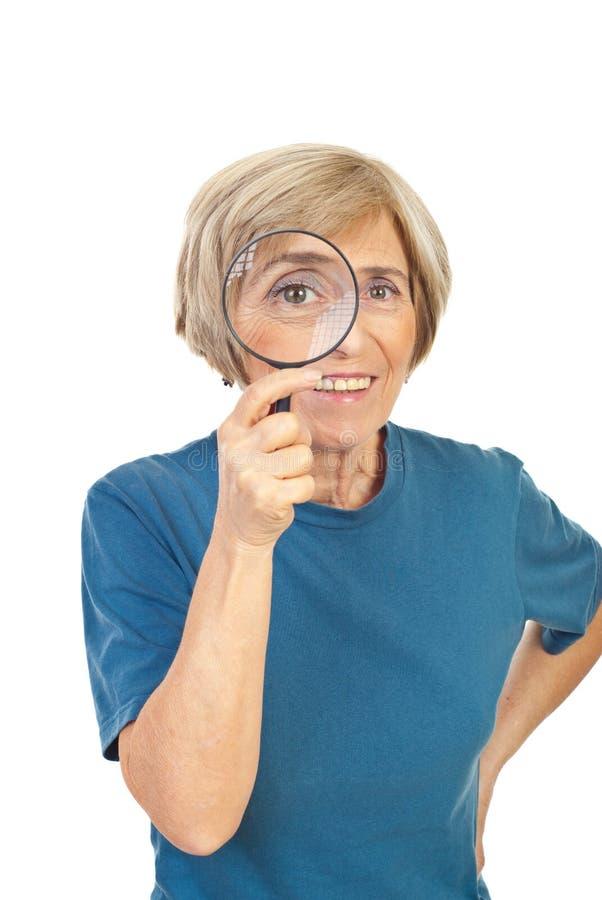 Mujer mayor divertida con la lupa imagen de archivo libre de regalías