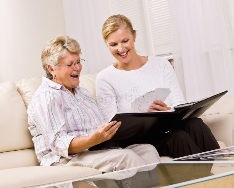 Mujer mayor e hija que miran las fotografías fotografía de archivo libre de regalías
